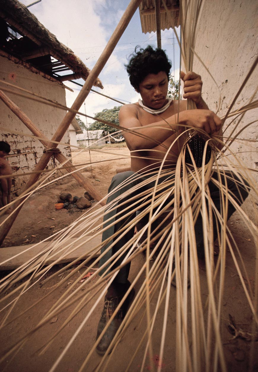"Ye´kuana man weaving a long basket or ""Tenke"" (sebucán), used to squeeze out the poisonous sap of the bitter yucca, a staple crop."