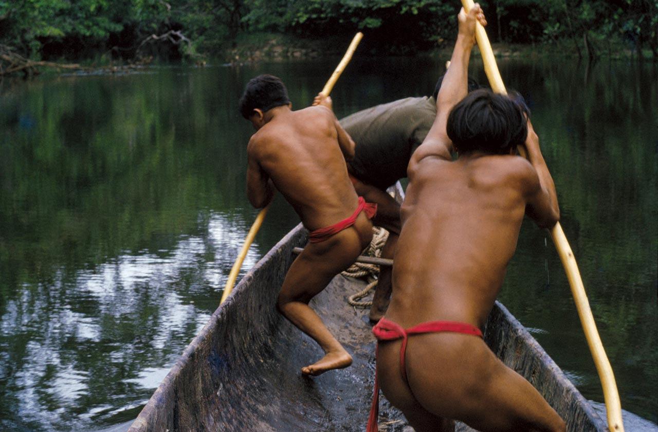 Sanemá Indians learning how to handle a curiara (canoe) built by the Ye´kwana, while traveling in shallow waters of the Cuchime River, Venezuela.